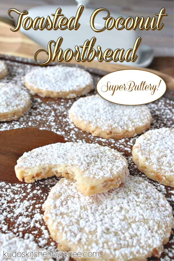 A vertical closeup title text image of Toasted Coconut Shortbread Cookies on a wooden tray with a bite taken out of one cookie.