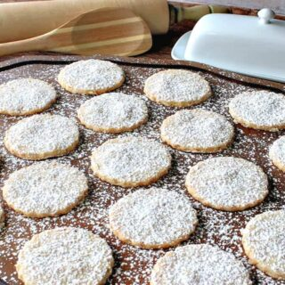 A wooden platter filled with Toasted Coconut Shortbread Cookies dusted with confectioners sugar.
