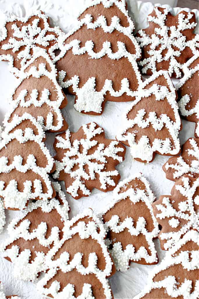 Super closeup vertical image of Gingerbread Trees and Snowflakes on a white background with royal icing and nonpareils.