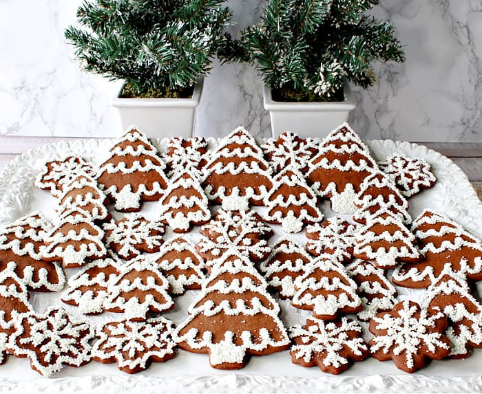 A horizontal photo of a white platter filled with pretty brown and white Gingerbread Trees and Snowflake Cookies for Christmas.