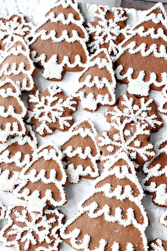 A vertical closeup picture of brown and white Gingerbread Cookies with royal icing and sanding sugar.