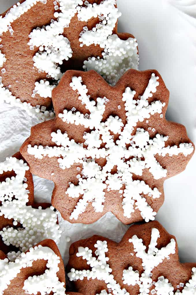 A super closeup vertical photo of a Gingerbread Snowflake Cookie with royal icing, white nonpareils, and white sanding sugar.