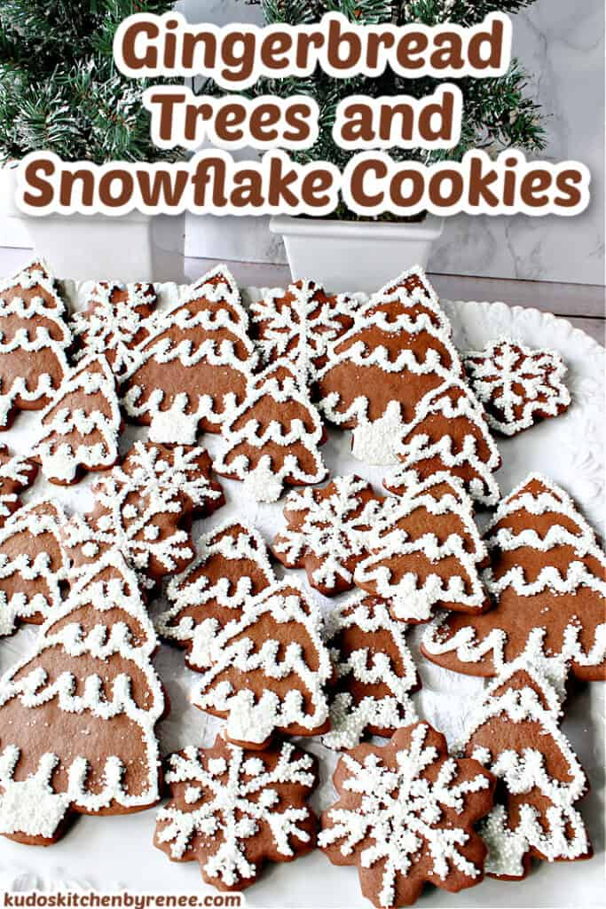 A vertical title text image of Gingerbread Trees and Snowflake Cookies on a white platter with snow covered pine trees in the background.