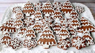 A large white platter filled with iced Gingerbread Trees and Snowflake Cookies with nonpareils and royal icing.