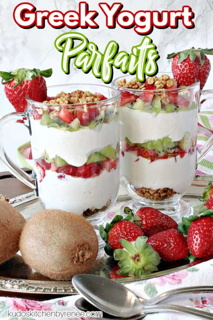 A vertical closeup image of two pretty Greek Yogurt Parfaits on a silver tray garnished with fresh strawberries and a title text overlay graphic.
