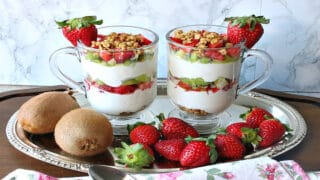 Two glass coffee cups filled with layered Greek Yogurt Parfait with kiwi and strawberries as garnish