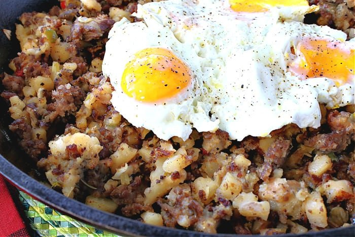 Closeup horizontal image of fried eggs on top of Grinch Who Hash.