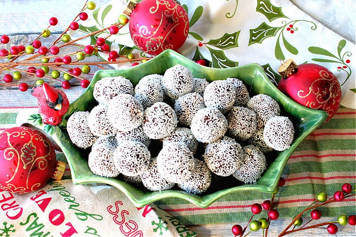 An overhead photo of a fun holly berry bowl filled with Nonpareil Chocolate Peppermint Truffles with ornaments and Christmas napkins in the background.
