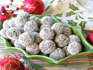 A cute holly berry bowl filled with Nonpareil Chocolate Peppermint Truffles with holiday napkins and ornaments on the side.
