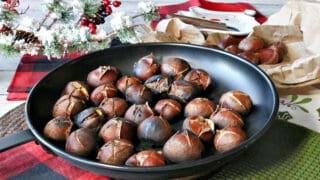 A bunch of cooked Roasted Chestnuts in a chestnut pan along with Christmas colored napkins and an evergreen bough