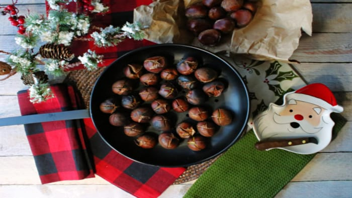 Direct overhead photo of Roasted Chestnuts in a chestnut pan along with a Santa dish, chestnut knife, and festive napkins.