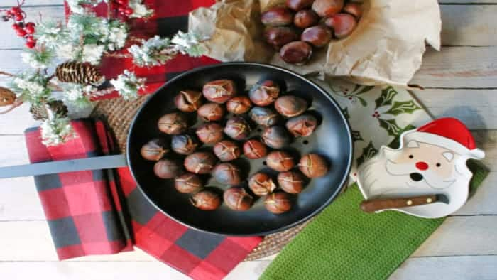 An overhead photo of a chestnut pan filled with Roasted Chestnuts along with some festive napkins and a chestnut knife.