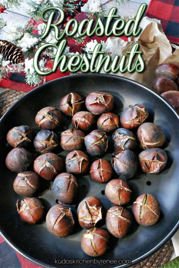 A vertical closeup image of split Roasted Chestnuts in a chestnut pan along with a snowy evergreen bough, and a title text overlay graphic.