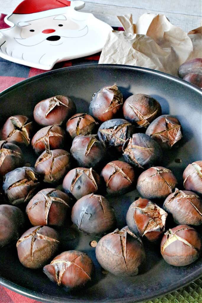 A vertical closeup image of Roasted Chestnuts in a chestnut pan along with a Santa dish in the background.