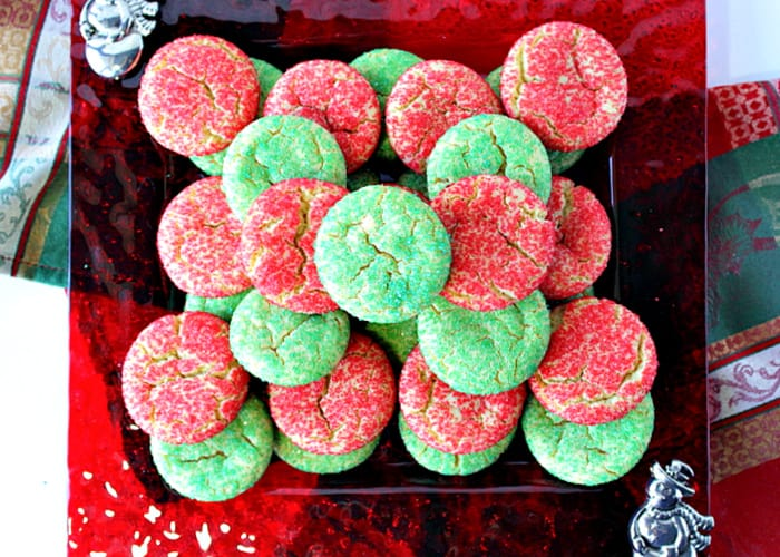 A direct overhead photo of a red glass plate filled with Santa's Favorite Sugar Cookies with red and green sugars.