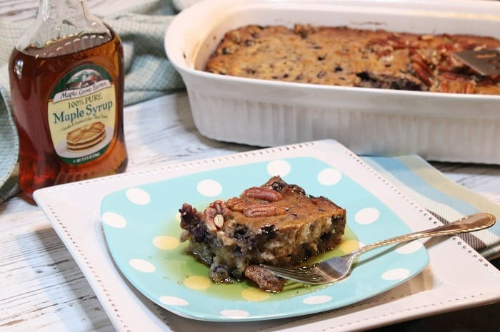 A square of Blueberry Sausage Breakfast Casserole on a blue polka dot plate with maple syrup.