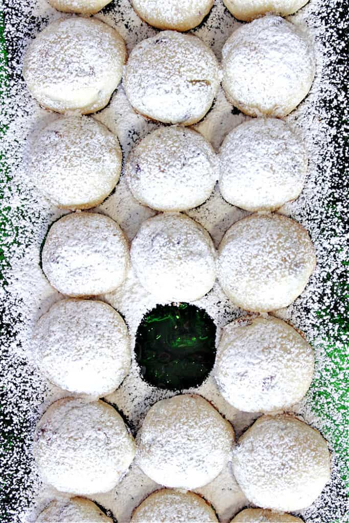 A vertical closeup of lined up snowballs cookies dusted with confectioners sugar with one missing