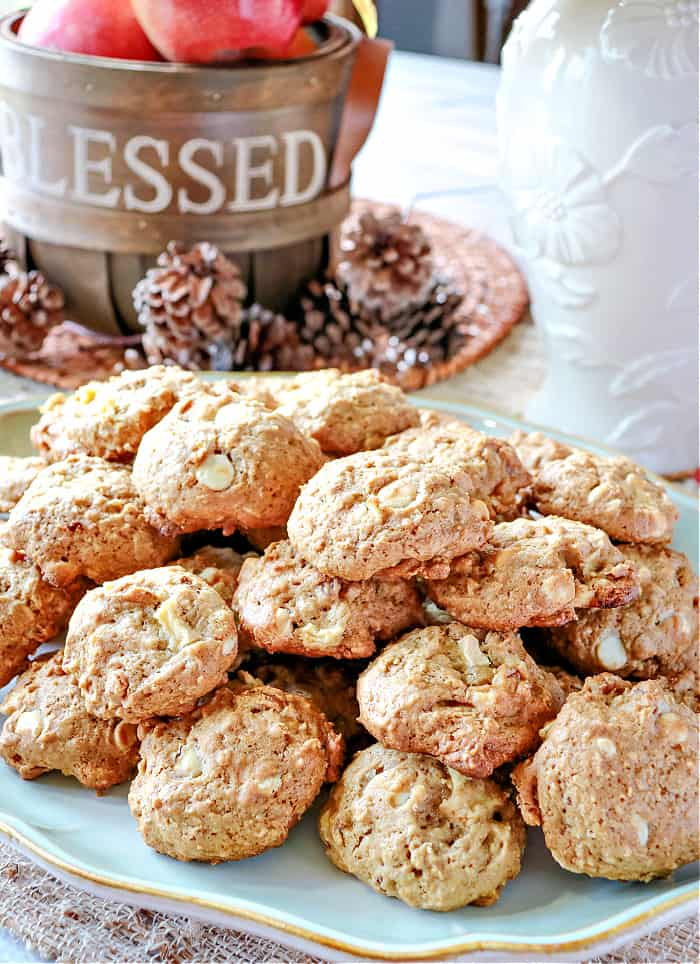 A vertical closeup image of a platter of Apple Oatmeal Cookies along with a basket and pinecones in the background.