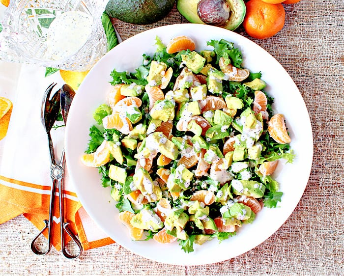 Direct overhead photo of a round white salad bowl filled with retro Avocado Orange Salad drizzled with orange poppy seed dressing.