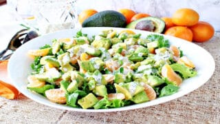 A horizontal photo of a green and orange Avocado Orange Salad in a large white bowl drizzled with poppy seed dressing.
