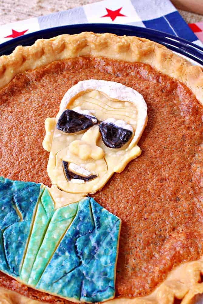 A closeup vertical offset photo of a Joe Biden Vinegar Pie with a painted pie crust.