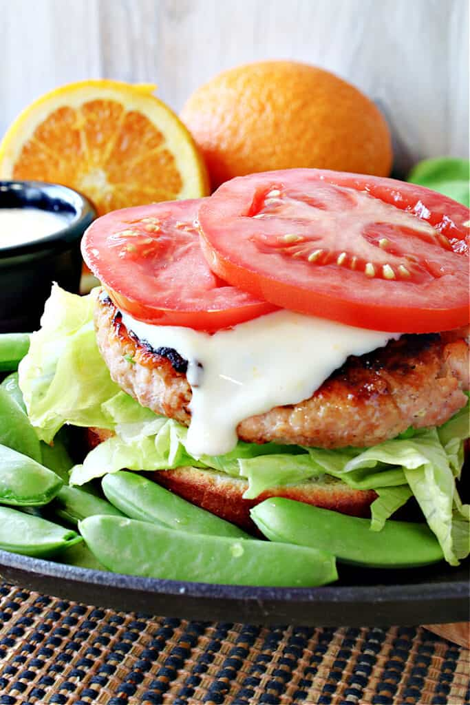A vertical closeup image of a Miso Salmon Burger without a top bun, but with tomato slices and honey orange sauce.