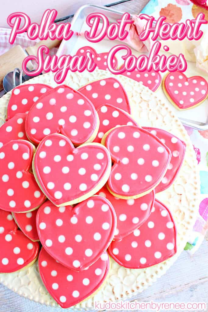 A vertical closeup of a cake plate filled with pink and white Polka Dot Heart Sugar Cookies along with a title text overlay graphic in pink and white.