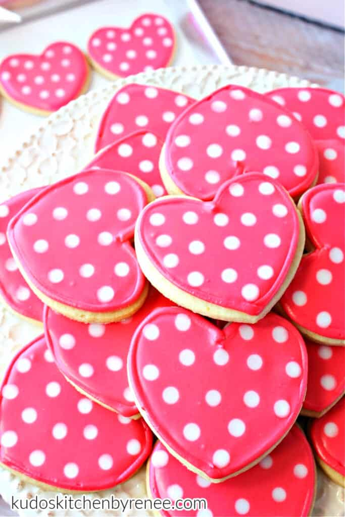 A vertical photo of a stack of Polka Dot Heart Cookies in pink and white along with two cookies on a baking sheet in the background.