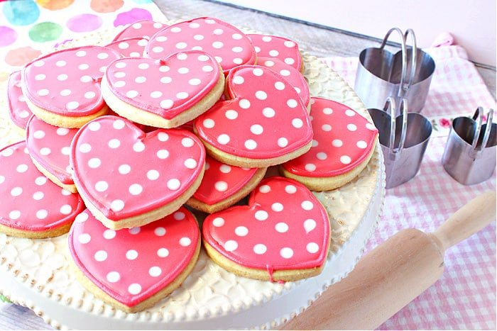 An offset horizontal photo of a cake stand filled with pink Polka Dot Heart Sugar Cookies with a rolling pin in the foreground and cookie cutters in the background.