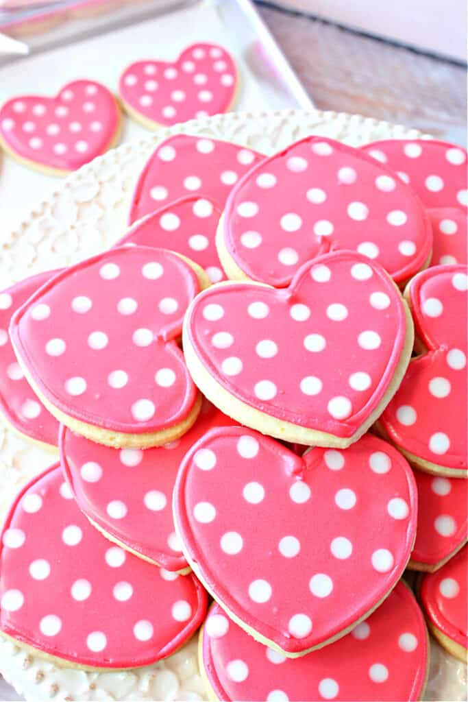 A vertical closeup overhead photo of a pile of pink Polka Dot Sugar Cookies on a platter with a few cookies on a cookie sheet in the background.