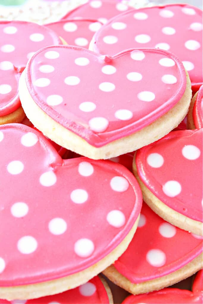 A closeup vertical side view of a plate of Polka Dot Heart Sugar Cookies with pink icing and white polka dots.