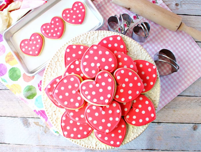 A direct overhead photo of a cake stand filled with pink and white Polka Dot Heart Cookies with a pink and white napkin and a multi colored polka dot napkin in the background.