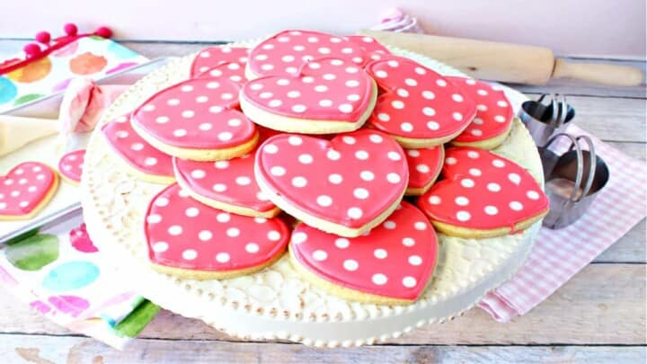 A round cake stand filled with pink Polka Dot Heart Sugar Cookies along with cookie cutters in the background.