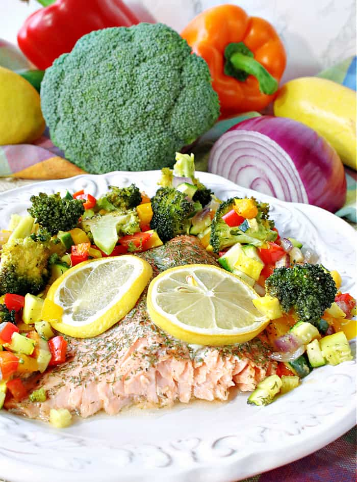 A Rainbow Trout on a white plate surrounded by colorful vegetables and topped with lemon slices.