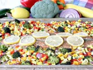 A sheet pan supper of Rainbow Trout with Rainbow Vegetables along with fresh veggies in the background.