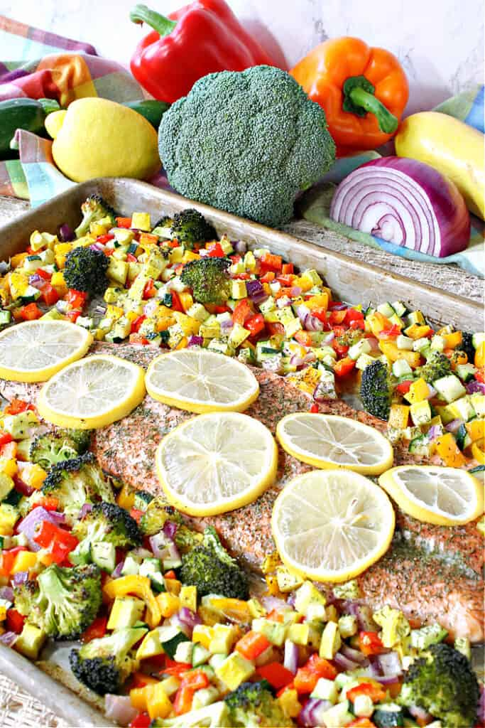 A colorful vertical photo of a sheet pan Rainbow Trout on a sheet pan surrounded by colorful roasted vegetables.