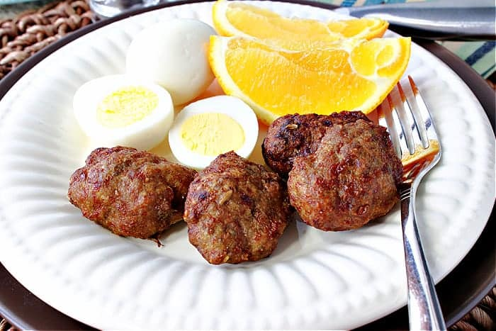 Air Fryer Turkey Breakfast Sausages on a white plate along with a hard boiled egg and orange slices.