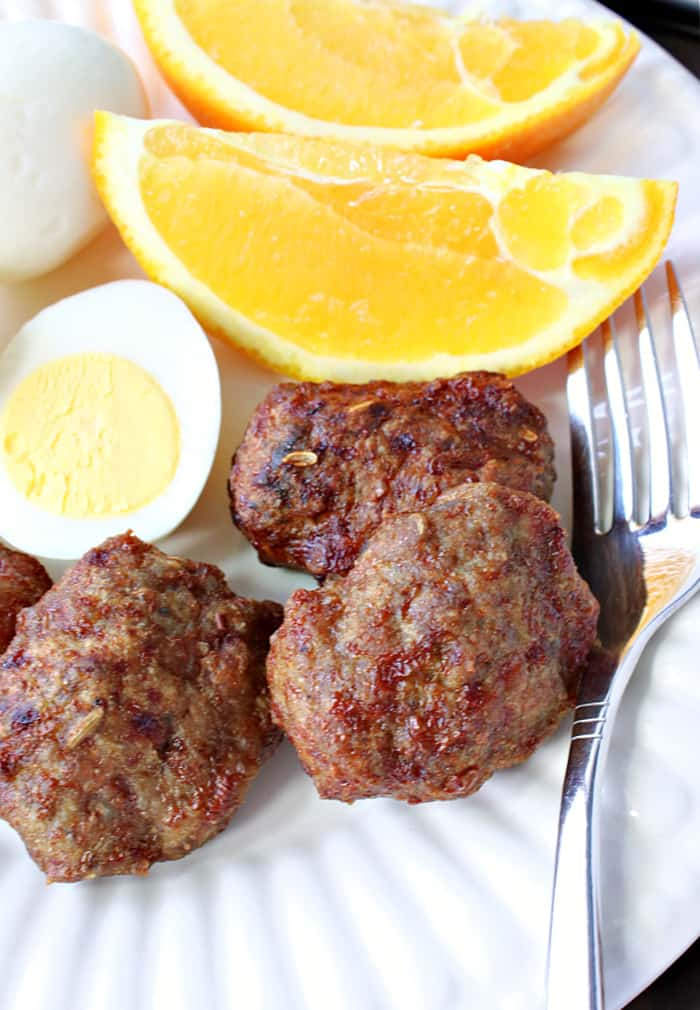 Vertical closeup image of air fryer Turkey Breakfast Sausage on a white plate with a hard boiled egg and some orange slices.