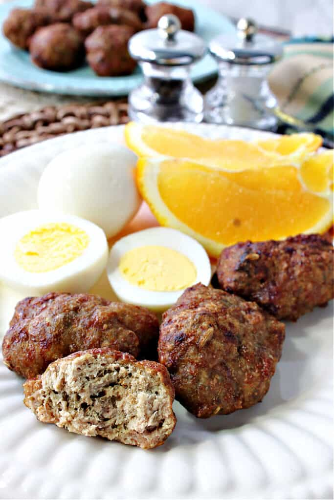 A closeup vertical image of the inside of a Turkey Breakfast Sausage along with a hard cooked egg and an orange slice on an white plate.