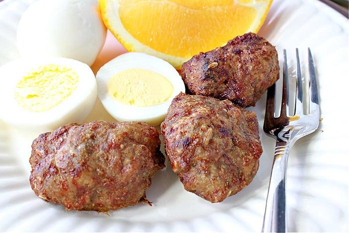 An overhead closeup photo of Turkey Breakfast Sausage on a plate with hard cooked eggs, a fork, and orange slices.