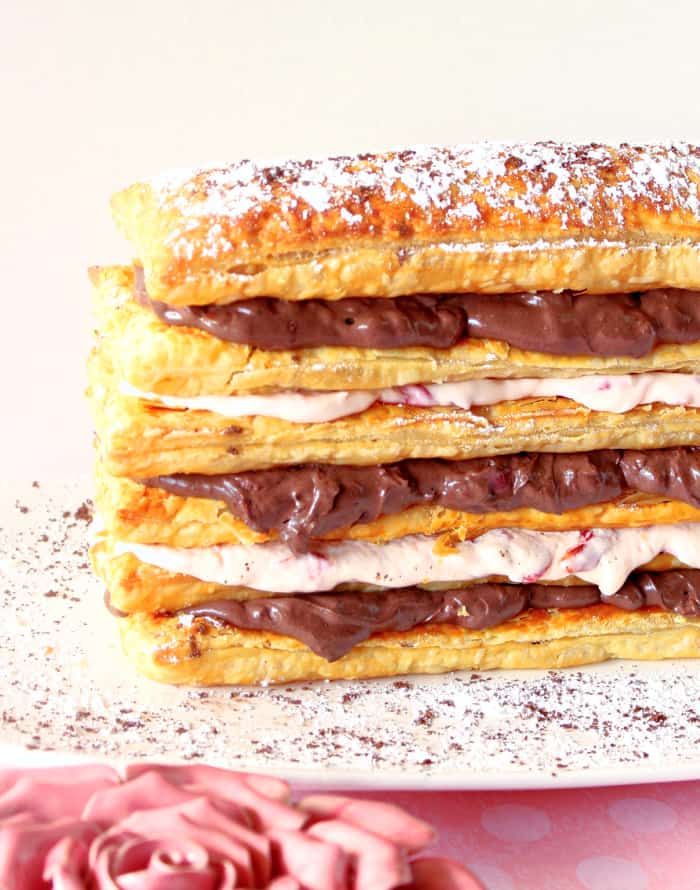 A closeup vertical image of a Chocolate Cherry Pastry Tower with layers of puff pastry and chocolate and cherry cream cheese filling.