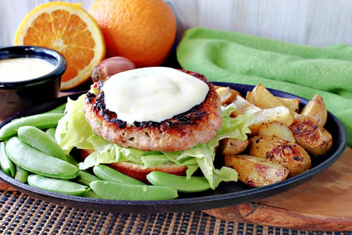 A Miso Salmon Burger without a top bun on a plate with honey orange sauce, sugar snap peas, and potatoes on the side.