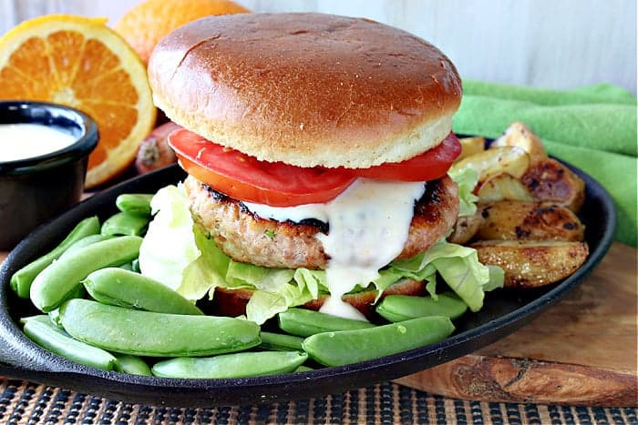 A Miso Salmon Burger on a plate with a bun, tomato, sauce, and sugar snap peas on the side.