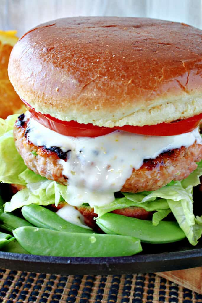 An extreme vertical closeup image of a Miso Salmon Burger with honey orange sauce, tomatoes, lettuce, and a bun.