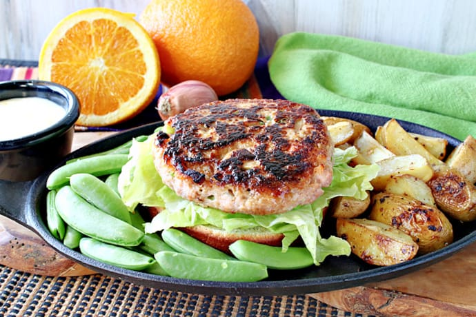 A horizontal photo of a Miso Salmon Burger on a plate surrounded by sugar snap peas and roasted potatoes.
