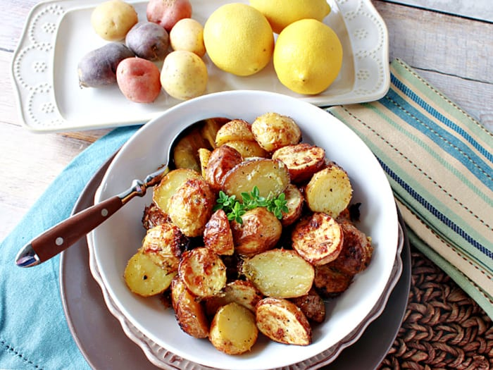Overhead horizontal photo of Roasted Baby Potatoes with Lemon and Thyme in a bowl with a spoon along with fresh lemons and potatoes in the background.