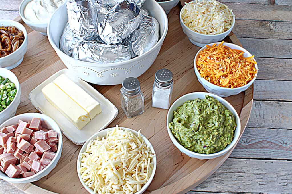 An offset horizontal photo of a large round wooden board with white bowls and topping for serving a Baked Potato Party Board.