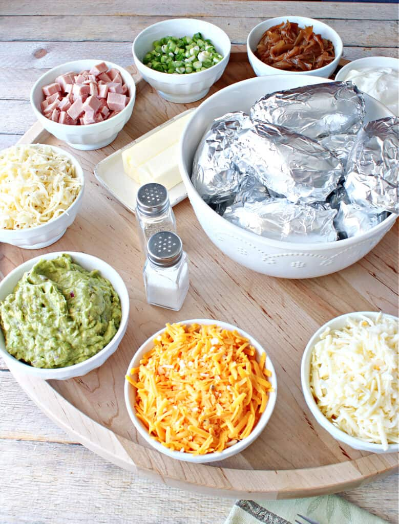 A vertical photo of a Baked Potato Party Board with foil wrapped potatoes in the center and potato toppings around the perimeter.