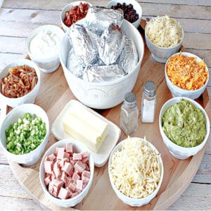 A large round wooden board loaded with the fixins for a Baked Potato Party Board.