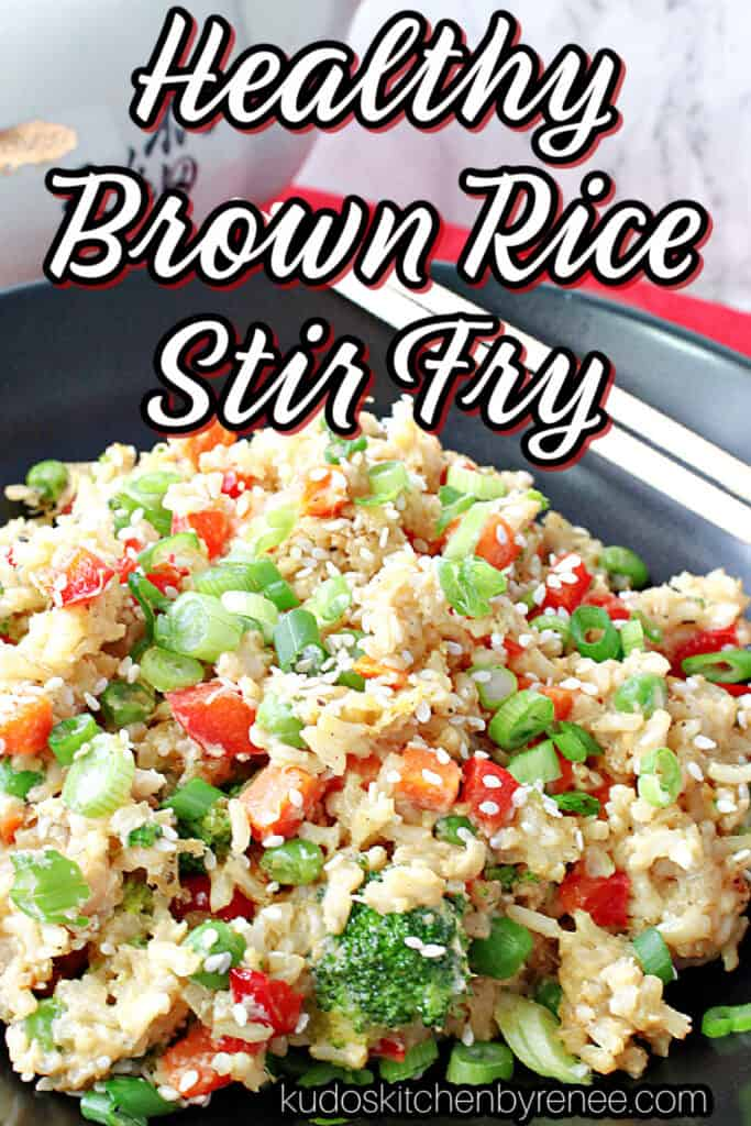 A vertical closeup of a healthy dish of Brown Rice Stir Fry with Vegetables and Eggs in a black bowl with a title text overlay graphic.
